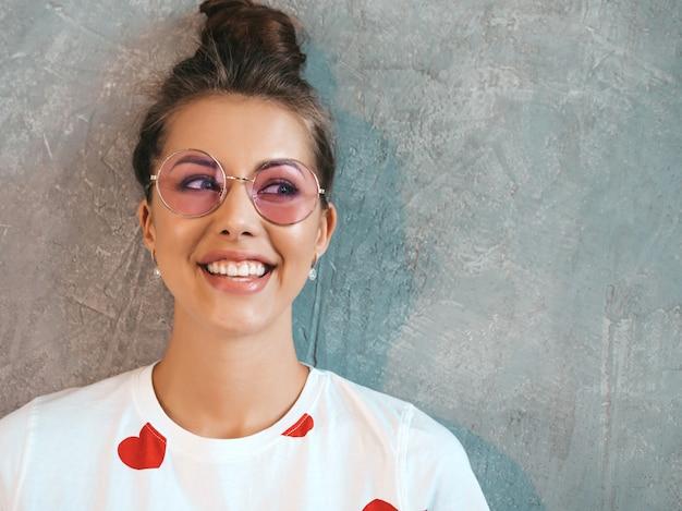 探している若い美しい笑顔の女性のクローズアップの肖像画。カジュアルな夏の白いドレスとサングラスでトレンディな女の子。