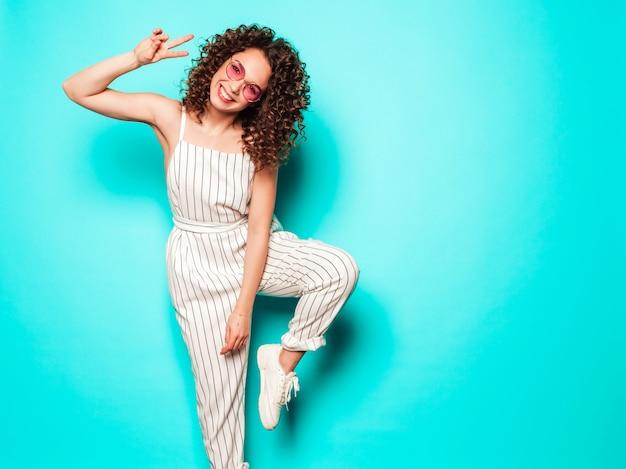 夏の流行に敏感な服を着たアフロカールの髪型と美しい笑顔モデルの肖像画。青い壁に近いポーズセクシーな屈託のない少女。トレンディな面白いと肯定的な女性