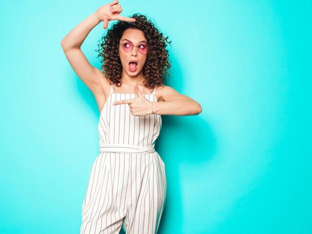 夏の流行に敏感な服を着たアフロカールの髪型と美しい笑顔のモデルの肖像画。水色の壁に近いポーズセクシーな屈託のない少女。手でフォトフレームを作る流行の女性