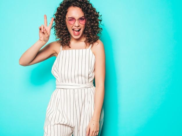 夏の流行に敏感な服を着たアフロカールの髪型と美しい笑顔モデルの肖像画。トレンディな面白いと肯定的な女性はピースサインを示しています