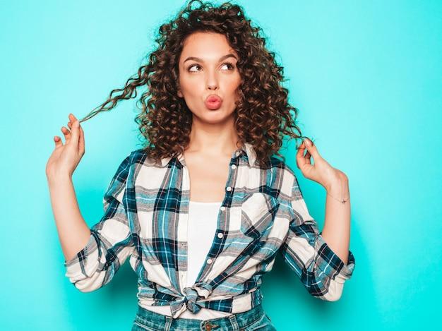 夏の流行に敏感な服を着たアフロカールの髪型と美しい笑顔のモデルの肖像画。流行の面白いと肯定的な女性