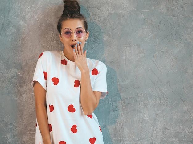 口の近くの手で見ている若い美しい驚く女性。カジュアルな夏の白いドレスのトレンディな女の子。