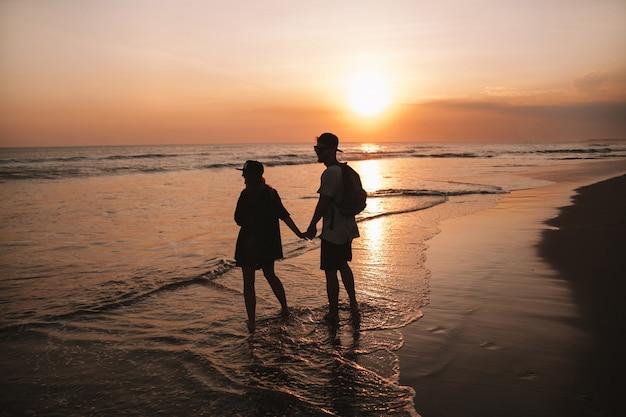 ビーチの上を歩くロマンチックなカップルのシルエットの肖像画。少女と彼女のボーイフレンドが黄金の色鮮やかな夕焼けでポーズ