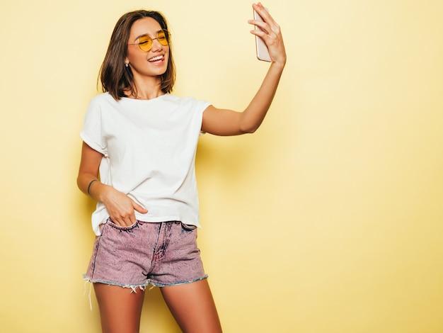 夏の流行に敏感な服を着た美しい笑顔のモデル。ジーンズのショートパンツで黄色の壁の近くのスタジオでポーズをとってセクシーな屈託のない少女。スマートフォンでセルフポートレート写真を撮るトレンディで面白い女性