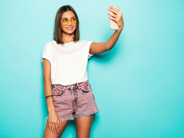 夏の流行に敏感な服を着た美しい笑顔のモデル。ジーンズのショートパンツで青い壁の近くのスタジオでポーズをとってセクシーな屈託のない少女。スマートフォンでセルフポートレート写真を撮るトレンディで面白い女性