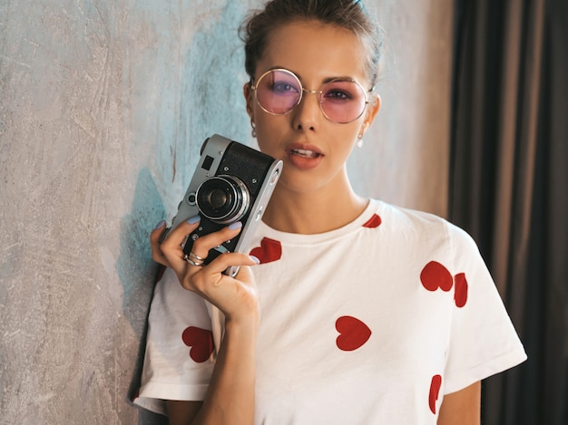 彼女のレトロなカメラを使用して写真を撮る美しい若い写真家の女の子
