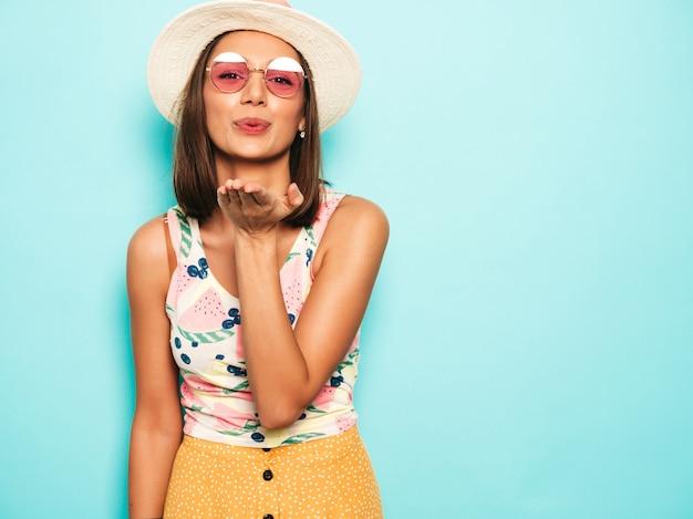 Молодая красивая женщина, глядя на камеру в шляпе. модная девушка в повседневной летней белой футболке и желтой юбке в круглых очках. позитивная самка показывает эмоции лица. воздушный поцелуй