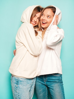 Две молодые красивые белокурые улыбающиеся хипстерские девочки в модной летней толстовке с капюшоном одеваются. сексуальные беззаботные женщины позируют возле синей стены. модные и позитивные модели с удовольствием