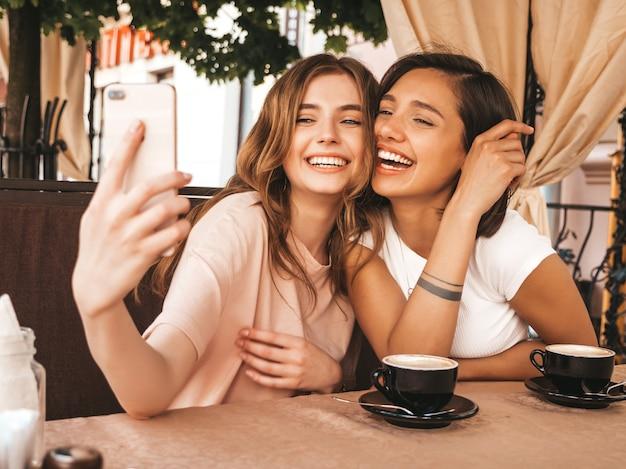 Две молодые красивые улыбающиеся битник девушки в модной летней одежде. беззаботные женщины в чате на веранде кафе и пить кофе. позитивные модели с удовольствием и и принимая селфи на смартфоне