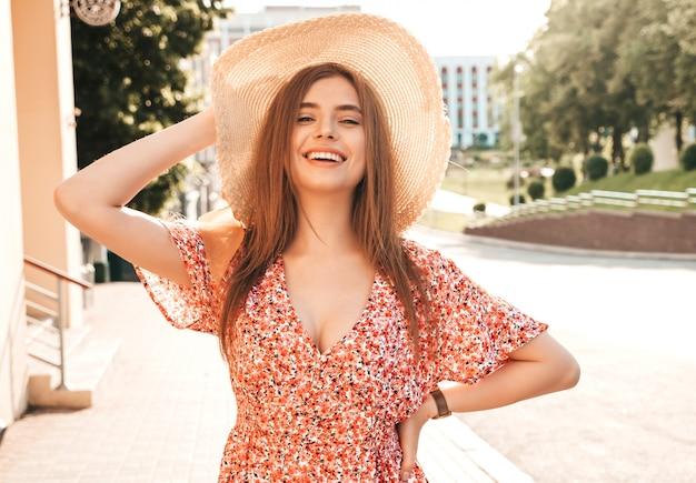 トレンディな夏のサンドレスで美しい笑顔の内気な少女の肖像画。セクシーな屈託のない女性が夕暮れ時の帽子で通りの背景にポーズします。屋外のポジティブモデル