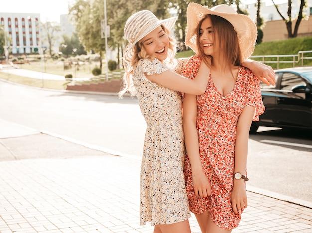 Две молодые красивые улыбающиеся битник девушки в модном летнем сарафане. сексуальные беззаботные женщины, позирует на фоне улицы в шляпах. позитивные модели развлекаются и обнимаются
