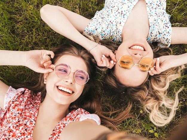 Две молодые красивые улыбающиеся хипстерские девушки в модном летнем сарафане. сексуальные беззаботные женщины, лежащие на зеленой траве в солнцезащитных очках. позитивные модели с удовольствием. вид сверху. принимая фото селфи на смартфоне