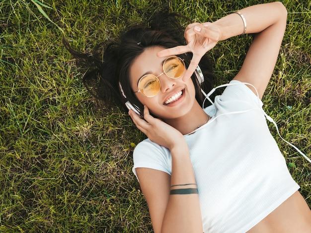 公園の芝生の上に横たわる若いスタイリッシュな流行に敏感な女性のファッションの肖像画。女の子はトレンディな服を着ています。笑顔のモデルは彼女の週末をお楽しみください。ヘッドフォンで音楽を聴く女性。
