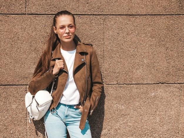 Портрет красивой брюнетки модели, одетой в летнюю хипстерскую куртку и джинсовую одежду