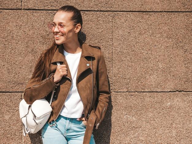 Портрет красивой улыбающейся модели брюнетки, одетой в летнюю куртку с хипстером и джинсовую одежду