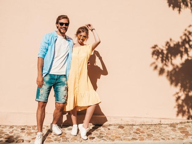 笑顔の美しい少女と彼女のハンサムなボーイフレンドの肖像画。カジュアルな夏のドレスを着た女性とジーンズの男。幸せな陽気な家族。壁の近くの通りで楽しんでいる女性