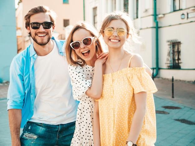 Группа молодых трех стильных друзей позирует на улице. мода мужчина и две милые девушки, одетые в повседневную летнюю одежду. улыбающиеся модели с удовольствием в солнцезащитных очках. веселые женщины и парень в сюзне