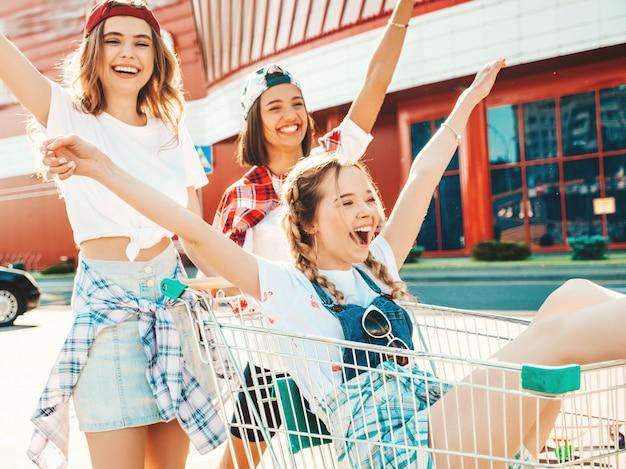 Три молодые красивые девушки веселились в продуктовой корзине