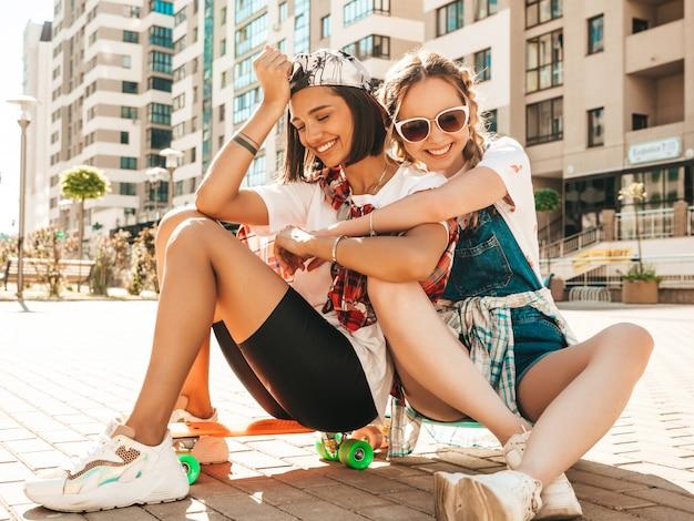 Две молодые улыбающиеся красивые девушки с красочными скейтборды пенни. женщины в летней одежде битник, сидя на улице фоне. позитивные модели развлекаются и сходят с ума