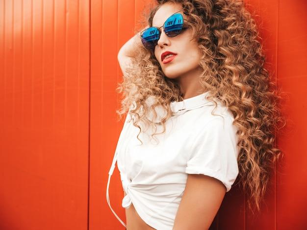 夏の流行に敏感な服を着たアフロカールの髪型と美しい笑顔のモデル。屋外の赤い壁に近いポーズセクシーな屈託のない少女。サングラスで楽しんで面白いと肯定的な女性
