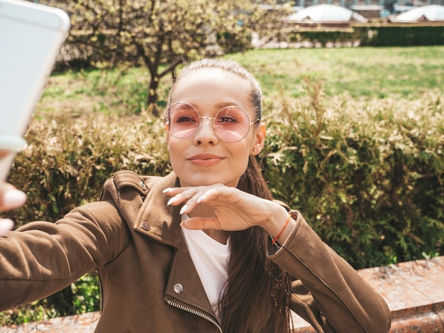 夏の流行に敏感なジャケットとジーンズで美しい笑顔ブルネットの少女の肖像画