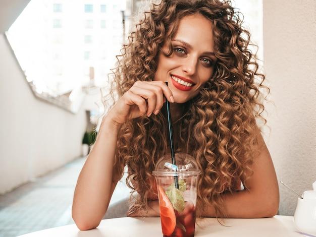 ストローでプラスチックカップで新鮮なスムージーを飲む女の子