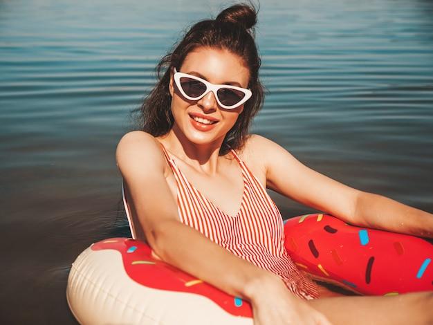 Красивая девушка в купальных костюмах плавает с надувным пончиком на море