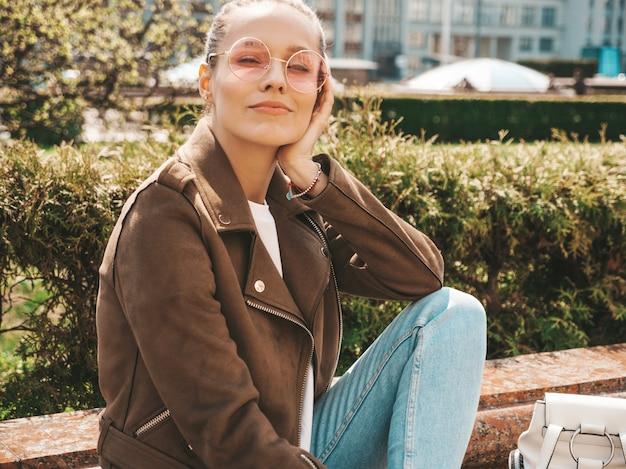 夏の流行に敏感なジャケットとジーンズの服に身を包んだ美しい笑顔ブルネットモデルの肖像通りのベンチに座っているトレンディな女の子