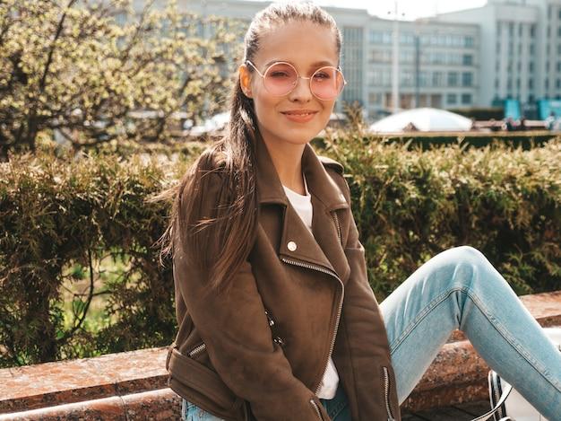 夏の流行に敏感なジャケットとジーンズの服に身を包んだ美しい笑顔ブルネットモデルの肖像ストリートのベンチに座っているトレンディな女の子