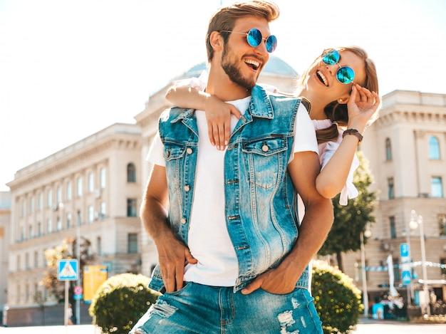 笑顔の美しい少女と通りを歩いて彼女のハンサムなボーイフレンド。