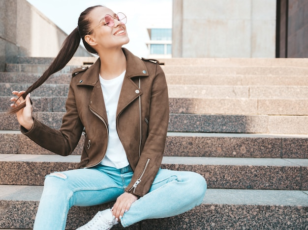 夏の流行に敏感なジャケットとジーンズの服に身を包んだ美しい笑顔ブルネットモデルの肖像画。通りの背景の手順の上に座ってトレンディな女の子。ラウンドサングラスで面白いと肯定的な女性
