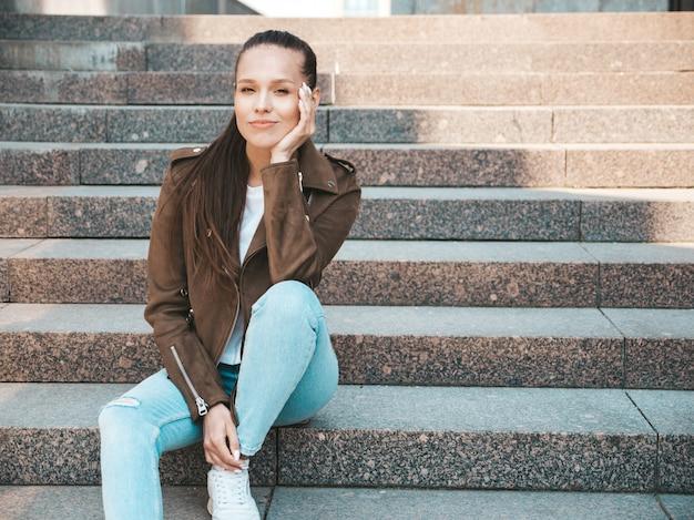 夏の流行に敏感なジャケットとジーンズの服に身を包んだ美しいブルネットモデルの肖像画。通りの背景の手順の上に座ってトレンディな女の子。面白いと肯定的な女性