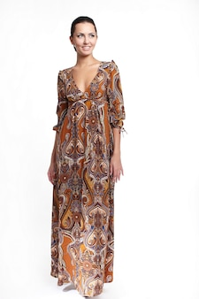 白の完全な長さで分離されたカラフルな茶色の夏のドレスの若い美しい笑顔の女性