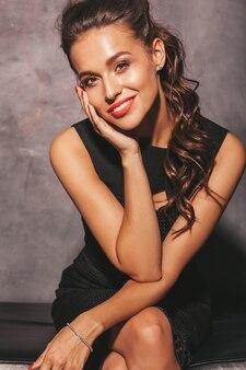 Портрет молодой красивой улыбающейся хипстерской женщины в модном летнем черном платье. сексуальная беззаботная женщина позирует возле стены. брюнетка модель с макияжем и прической. сидя на стуле