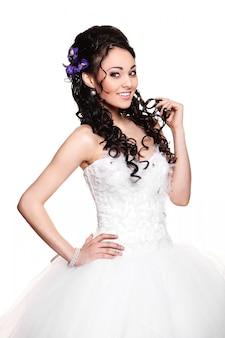 Счастливая сексуальная красивая невеста брюнетка женщина в белом свадебном платье с прической и ярким макияжем
