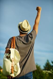 Задняя часть молодого привлекательного современного стильного человека в вскользь ткани в шляпе в очках за голубым небом
