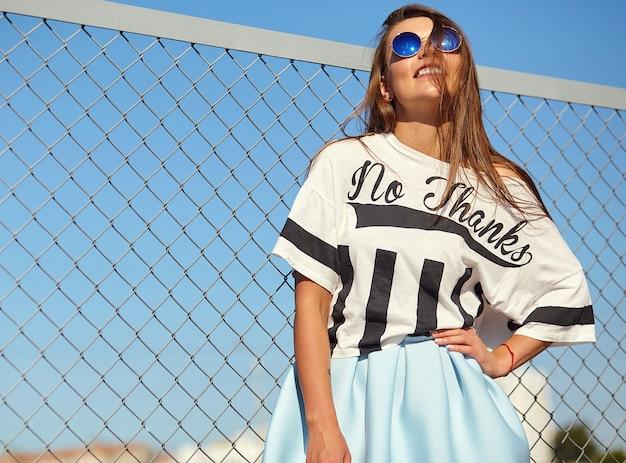 鉄の格子と青い空の後ろの通りでポーズをとって明るい流行に敏感な夏のカジュアルな服で面白いクレイジーグラマースタイリッシュな笑顔の美しい若い女性モデルの肖像画