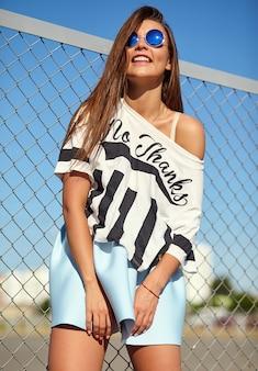 Портрет смешного сумасшедшего гламура стильной улыбающейся красивой молодой женщины модели в яркой хипстерской летней повседневной одежде, позирующей на улице за железной решеткой и голубым небом