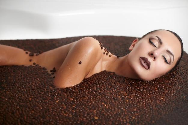 コーヒーとジャグジーで美しいファッションの女性の肖像画。ボディケア。明るいメイク