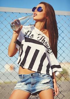 鉄格子と青空の背後にある通りでポーズをとって明るい流行に敏感な夏のカジュアルな服でセクシーなグラマースタイリッシュな美しい若い女性モデルの肖像画。ボトルから水を飲む