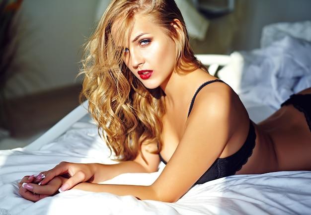 Фасонируйте портрет модели красивой сексуальной молодой взрослой белокурой женщины нося черное эротичное женское бельё лежа на кровати на заходе солнца