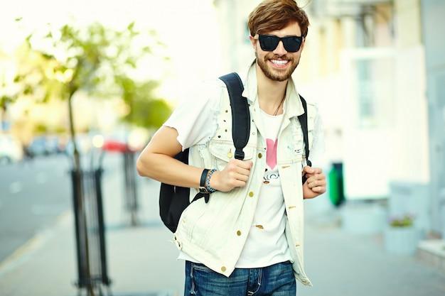 Смешной улыбающийся битник красавец в стильной летней одежде на улице в темных очках