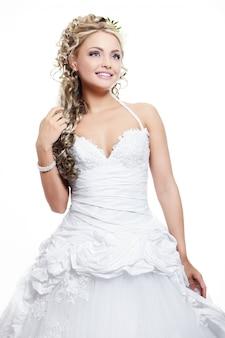 Счастливая улыбающаяся красивая невеста в белом свадебном платье с прической и ярким макияжем