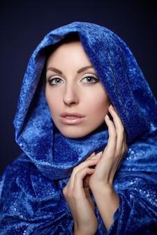 暗いに分離された青い色の布で美しい女性のクローズアップの肖像画明るいメイク