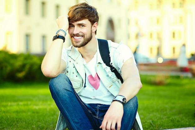 Смешной улыбающийся битник красавец парень в стильной летней одежде на улице в солнцезащитные очки