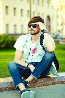 Смешной улыбающийся битник красавец парень в стильной летней одежде на улице, сидя на траве в парке