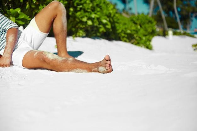 流行に敏感な夏の帽子を着て砂浜に横たわっているスタイリッシュな若い男性モデル男