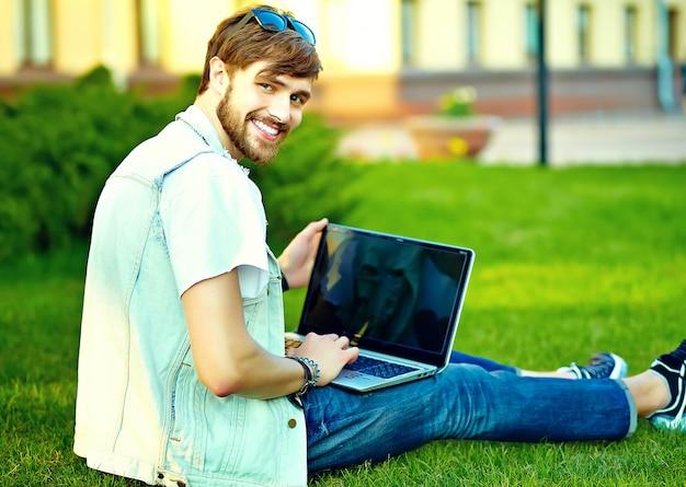 Смешной улыбающийся битник красавец парень в стильной летней одежде на улице позирует сидя на траве с ноутбуком