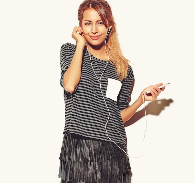 ヘッドフォンでスマートフォンで音楽を聴く白で隔離されるカジュアルな流行に敏感な夏服で美しい幸せな女