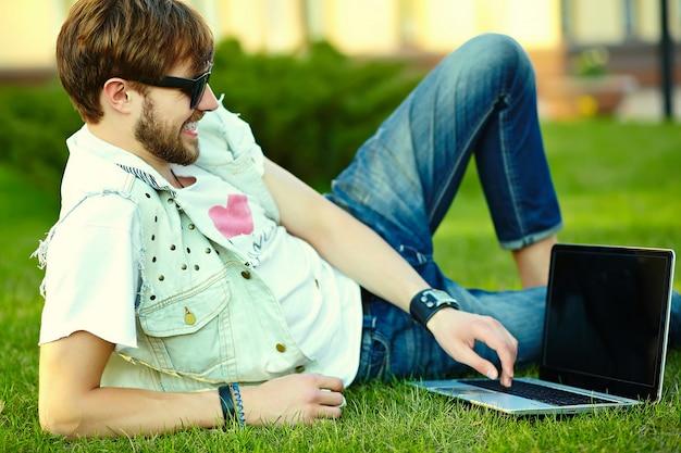 Смешной улыбающийся битник красавец парень в стильной летней ткани в траве с ноутбуком